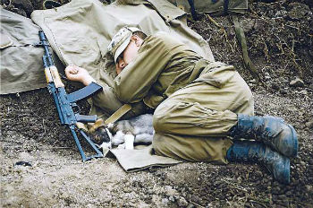 Рядом с солдатом в клубок свернулся щенок, которого накануне ранило. Военные перевязали собаку и прозвали Фугасом